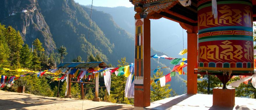 bhutan_view_of_the_taktshang_monastery_in_paro_with_prayer_flags_and_a_prayer_wheel_in_the_front_copy_0