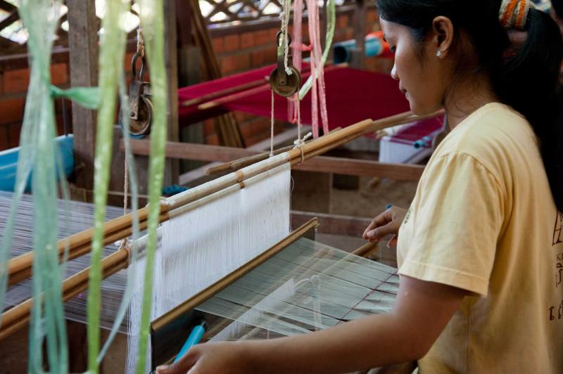 cambodia_a_weaver_adjusts_the_silk_cloth_on_her_loom_siem_reap-e_1