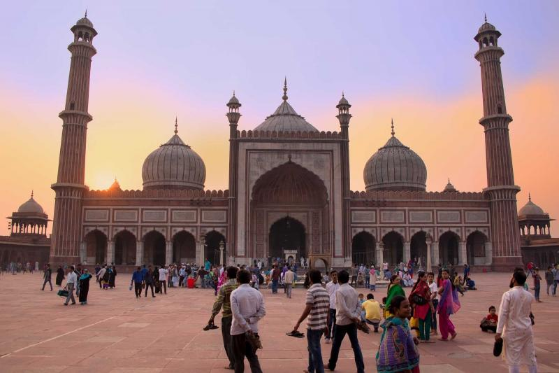 india_delhi_unidentified_people_walk_in_the_courtyard_of_jama_masjid_at_sunset-e