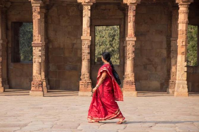 india_delhi_unidentified_woman_walks_in_quwwat-ul-islam_mosque_courtyard_at_qutub_minar_complex_e
