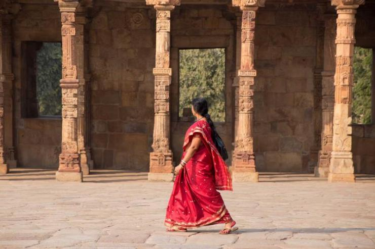 india_delhi_unidentified_woman_walks_in_quwwat-ul-islam_mosque_courtyard_at_qutub_minar_complex_e
