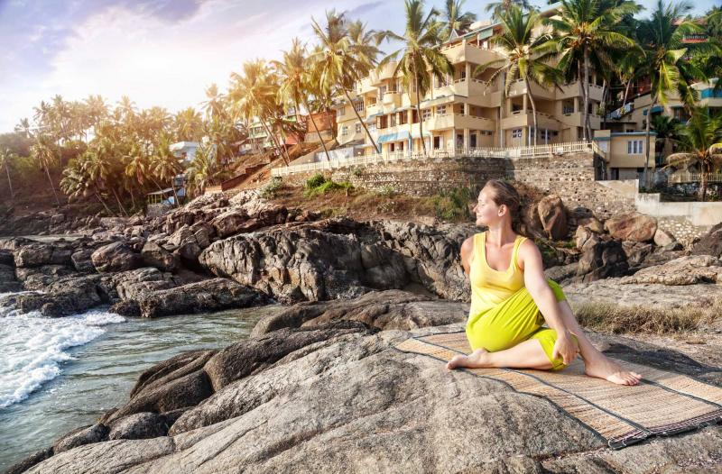 india_kovalam_kerala_yoga_by_woman_in_yellow_costume_on_the_stone_nearby_ocean_and_tropical_resort_in_kovalam