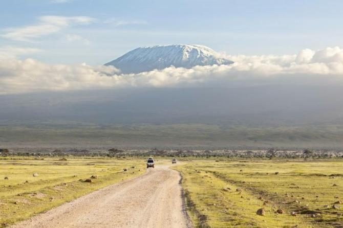 africa_kenya_tanzania_kilimanjaro_with_snow_cap_seen_from_amboseli_national_park_in_kenya_with_a_road_in_the_foreground_0