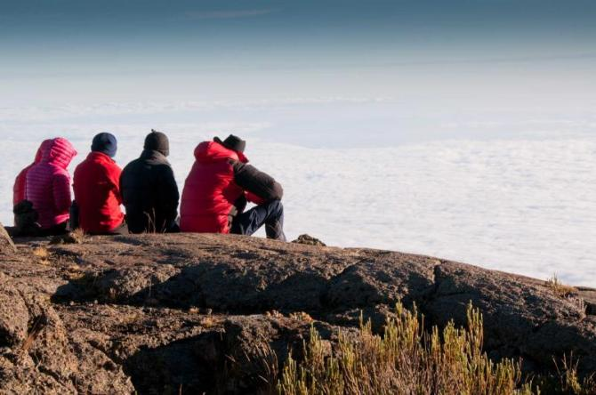 africa_tanzania_a_team_of_trekkers_gazing_over_the_early_morning_clouds_on_the_trek_to_kilimanjaro_summit_1