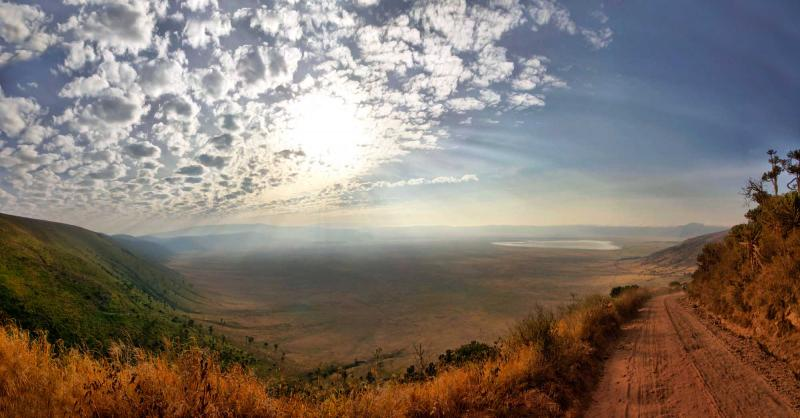 africa_tanzania_ngorongoro_panorama_of_ngorongoro_crater_with_sunny_blue_sky_with_few_clounds_and_gravel_road_1