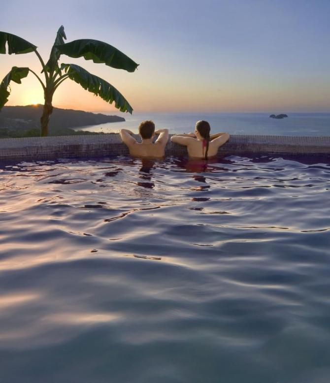 costa_rica_young_couple_watches_the_sunset_from_an_oceanside_pool_in_costa_rica